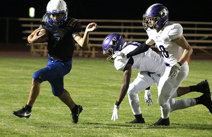 Kingman High's Danny Dias evades Wickenburg defenders Friday night. Dias later caught a 79-yard touchdown and finished with 105 yards receiving.