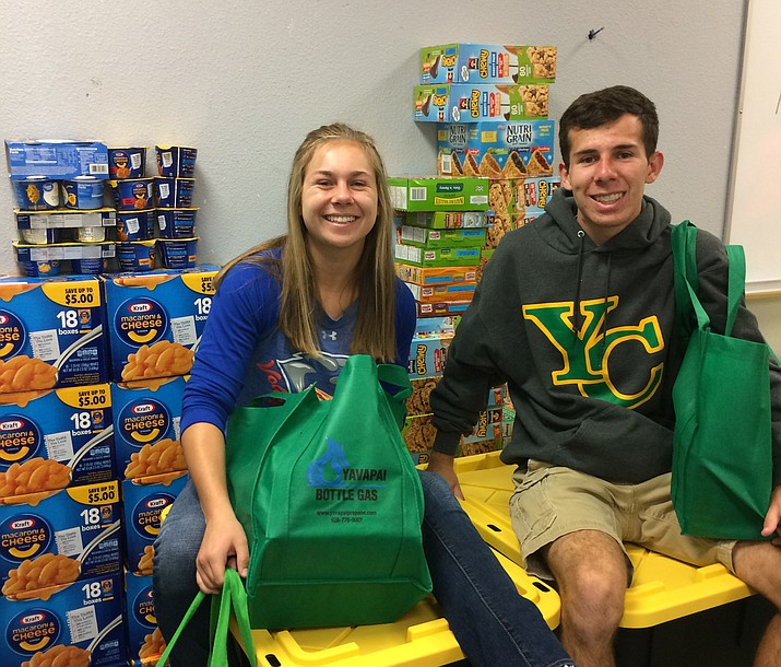 Alex and Addie sitting surrounded by some 200 food bags filled with a literal ton of non-perishable food items– the weight was 2,000 pounds. (Nanci Hutson/Courier)