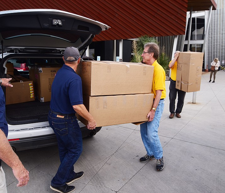 Volunteers load up a vehicle with some of the jackets that are part of the Noon Lions Club and Knights of Columbus Coats for Kids program Tuesday, Oct. 23, 2018 in Prescott Valley. The group filled 57 boxes with 750 jackets for 14 school districts and charter schools in Yavapai County. (Les Stukenberg/Courier)