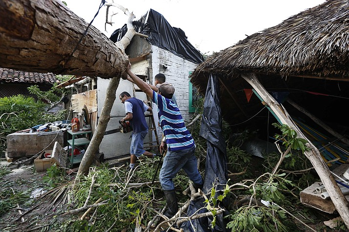 A resident works to remove a felled tree in the aftermath of Hurricane Willa, in Escuinapa, Mexico, Wednesday, Oct. 24, 2018. There were no immediate reports of deaths, but the storm's 120 mph winds knocked out power and damaged buildings in the Sinaloa state municipality of Escuinapa. (Marco Ugarte/AP)