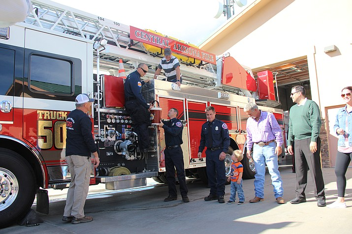 Central Arizona Fire and Medical Authority personnel christen their brand new ladder truck by splashing water onto it during a dedication ceremony Wednesday, Oct. 24. The water used was taken from the agency's old ladder truck to symbolize a transfer of responsibility. (Max Efrein/Courier)