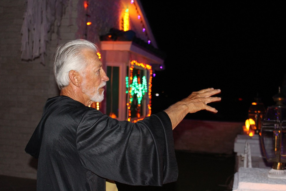 David Preston, in costume for Halloween, points to the work that went into putting up more than 25,000 lights for his display at 661 Shadow Mountain Drive. (Photo by Hubble Ray Smith/Daily Miner)