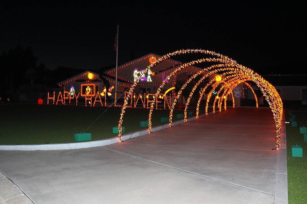 """The Preston home at 661 Shadow Mountain Drive features a lighted """"Happy Halloween"""" sign in the yard and arches over the driveway, along with decorations on the wall. (Photo by Hubble Ray Smith/Daily Miner)"""