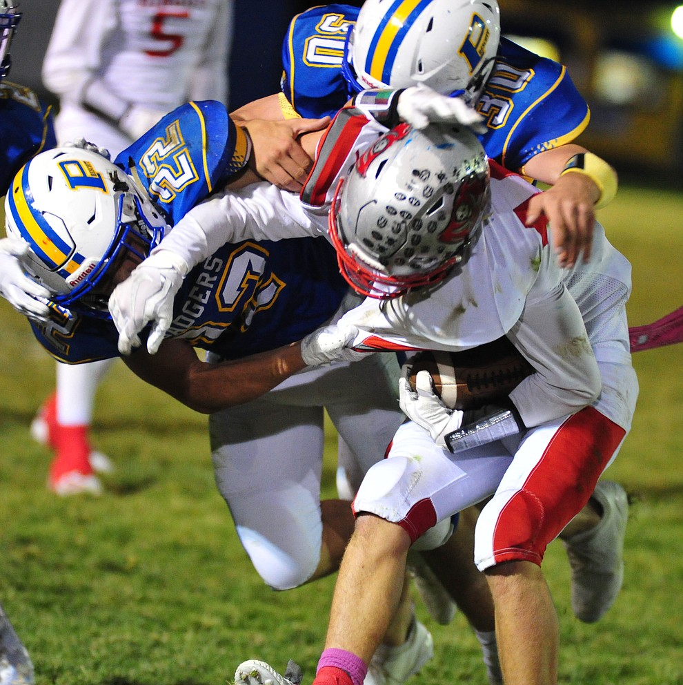 Prescott's Colton Amos and Dylan Davis make a stop on Alex Nelson as the Badgers play cross mountain rival Mingus for the region title Friday, Oct. 26, 2018 in Prescott. (Les Stukenberg/Courier).