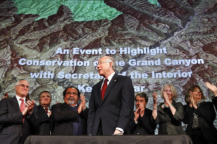 In this Jan. 9, 2012 file photo, then Interior Secretary Ken Salazar, center, standing in front of a map of the Grand Canyon, is applauded after announcing a twenty year ban on new mining claims near the Grand Canyon in Washington. A federal appeals court has revived a challenge to a company's right to mine uranium near the Grand Canyon. The 9th U.S. Circuit Court of Appeals on Thursday, Oct. 25, 2018, said a lower court must determine whether the U.S. Forest Service erred in finding that Energy Fuels had a valid, existing right to mine outside the national park's South Rim entrance. Environmentalists and the Havasupai Tribe had challenged the Forest Service's decision. (AP Photo/Jacquelyn Martin, File)