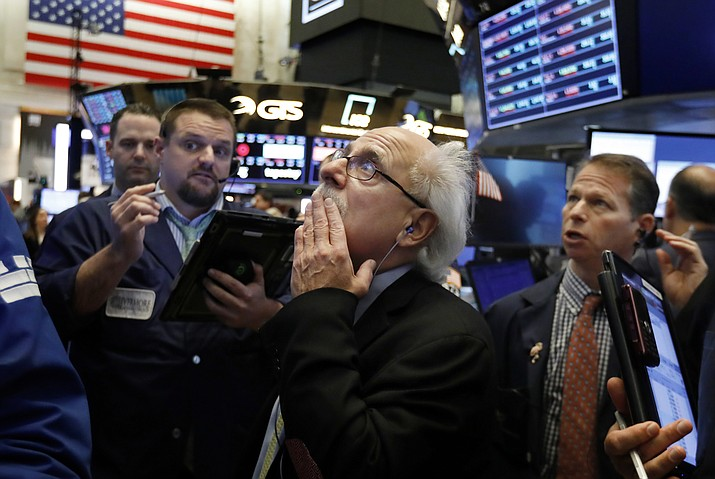 Peter Tuchman, center, works with fellow traders on the floor of the New York Stock Exchange, Friday, Oct. 26, 2018. Stocks are opening broadly lower on Wall Street, a day after a massive surge, as a number of big companies reported disappointing results. (Richard Drew/AP)