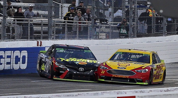 Joey Logano (22) and Martin Truex Jr. (78) make contact as they approach the finish line at the Monster Energy NASCAR Cup Series auto race at Martinsville Speedway in Martinsville, Va., Sunday, Oct. 28, 2018. Logano won the race. (Steve Helber/AP)
