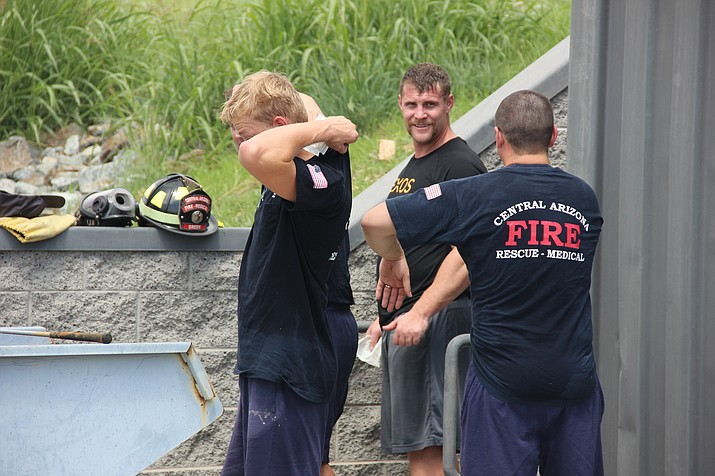 Local firefighters wipe sweat and smoke residue from their necks, armpits and groins after a training exercise in September that involved them being exposed to smoke. (Max Efrein/Courier)
