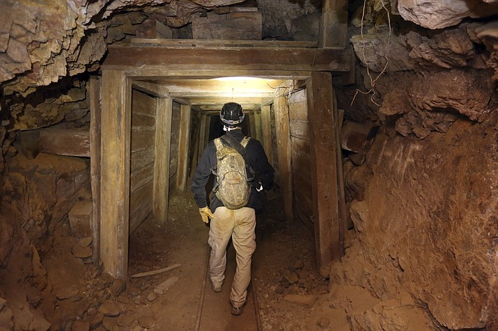 "Jeremy MacLee walks through a mine near Eureka, Utah, on Aug. 14, 2018. Underneath the mountains and deserts of the U.S. West lie hundreds of thousands of abandoned mines. Still, not everyone wants to see the mines closed. ""Nobody has walked the path you're walking for 100 years,"" said MacLee, who uses old mining documents and high-tech safety equipment to find and explore forgotten holes, mostly in Utah. He also lends his expertise to searches for missing people. (Rick Bowmer/AP, File)"