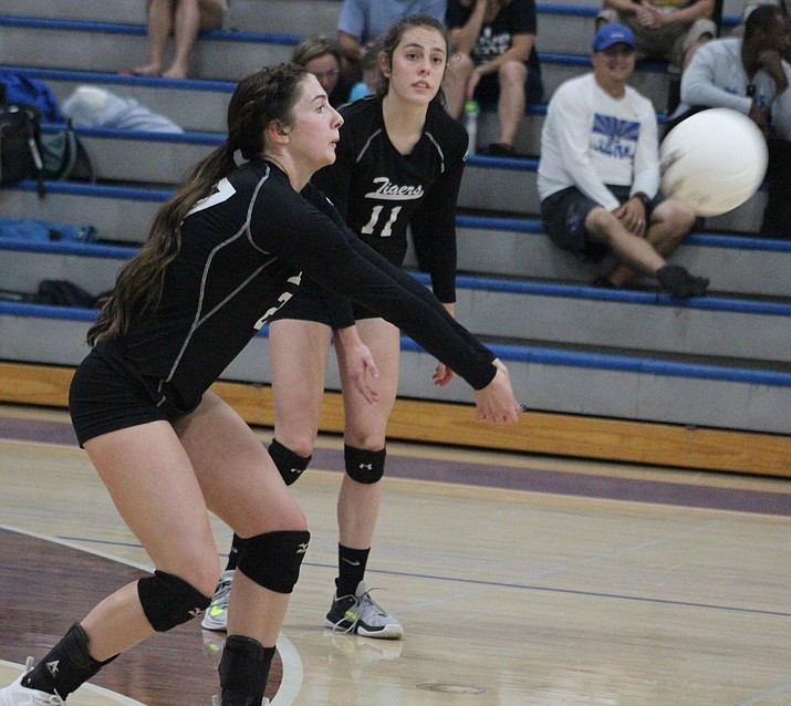 Kingman Academy's Isabella Anderson passes the volleyball Tuesday as fellow senior Grace Herbine looks on during a 3A Conference Play-In match at Valley Christian. (Photo by Beau Bearden/Daily Miner)