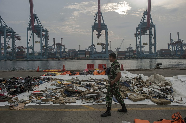 An Indonesian soldiers walk past debris retrieved from the waters where Lion Air flight JT 610 is believed to have crashed at Tanjung Priok Port in Jakarta, Indonesia, Wednesday, Oct. 31, 2018. (Fauzy Chaniago/AP)