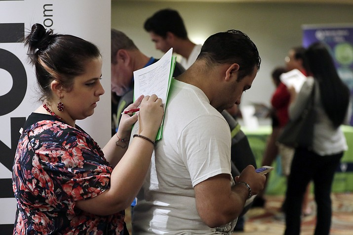 In this Jan. 30, 2018, file photo, Loredana Gonzalez, of Doral, Fla., fills out a job application at a JobNewsUSA job fair in Miami Lakes, Fla. On Friday, Nov. 2, the U.S. government issues the October jobs report. (AP Photo/Lynne Sladky, File)