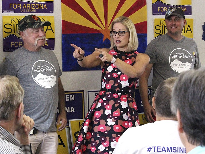 "Democratic Senate candidate Kyrsten Sinema talks to volunteers at a get-out-the-vote phone bank in Phoenix, Ariz., alongside members of the ""Veterans for Sinema"" group in this Thursday, Nov. 1, 2018 photo. (AP Photo/Bob Christie)"