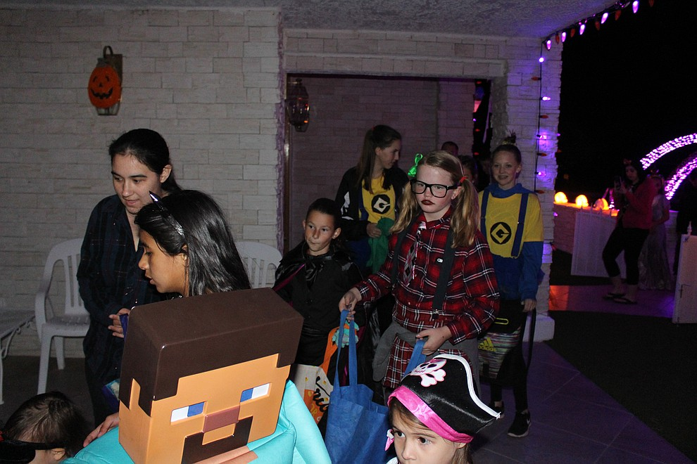 Trick-or-treaters line up for full-size candy bars that were handed out at the Preston's home.