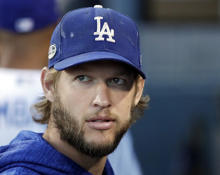 In this Oct. 16, 2018 file photo, Los Angeles Dodgers pitcher Clayton Kershaw watches before Game 4 of the National League Championship Series against the Milwaukee Brewers in Los Angeles. The Dodgers and three-time Cy Young Award winner Kershaw reached an agreement on a contract extension Friday, Nov. 2, 2018, that will keep the seven-time All-Star with the club through 2021. (Jae C. Hong/AP, file)