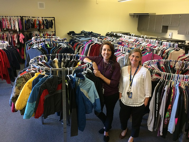 Kelly Lee, Family and Community Engagement coordinator, left, and Helene Tonnemacher, Family Resource specialist and Homeless liaison, stand in the midst of racks of clothing in the Family Resource Center on Oct. 25. (Sue Tone/Tribune)