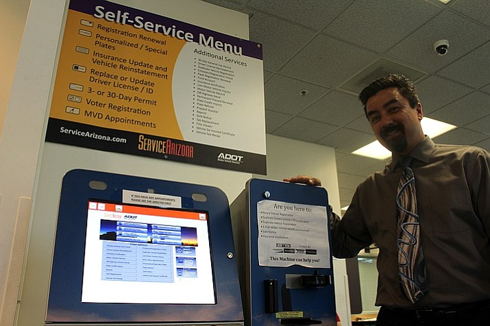Tim Mahan, manager of the Kingman AZDOT facility, stands next to the kiosk that customers can utilize to renew their car registration, register to vote and more. (Photo by Vanessa Espinoza/Daily Miner)