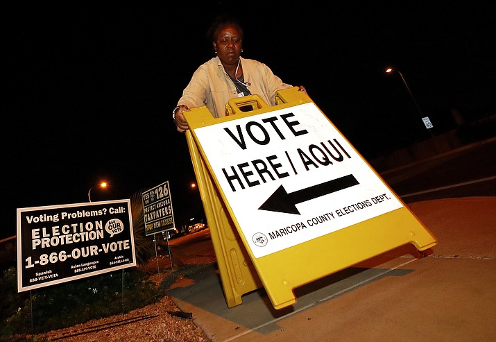 "Maricopa County elections official Deborah Atkins places a ""vote"" sign outside a polling station prior to it's opening, Tuesday, Nov. 6, 2018, in Phoenix. (Matt York/AP)"