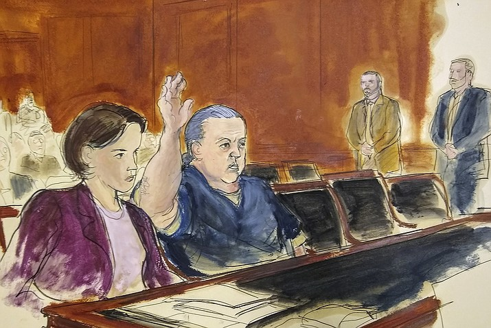 In this courtroom sketch, pipe bombs suspect Cesar Sayoc seated in court, raises his arm to swear to the truth of his statement of need for assigned counsel, during his presentment in Manhattan Federal Court Tuesday, Nov. 6, 2018, in New York. (Elizabeth Williams via AP)