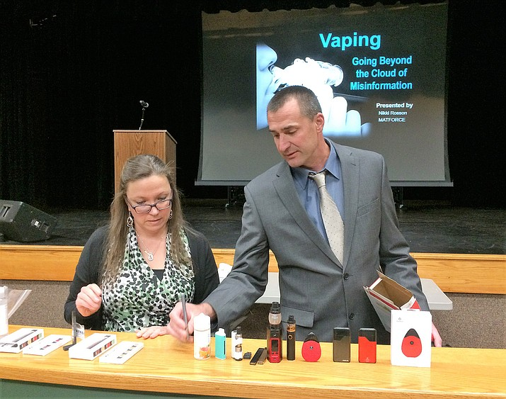 Nikki Rosson, left, executive assistant with MATFORCE, and Rick Bradshaw, Dean of Students at Bradshaw Mountain High School, display items used in vaping Nov. 5 at Glassford Hill Middle School as part of a presentation on the dangers of vaping. (Sue Tone/Tribune)