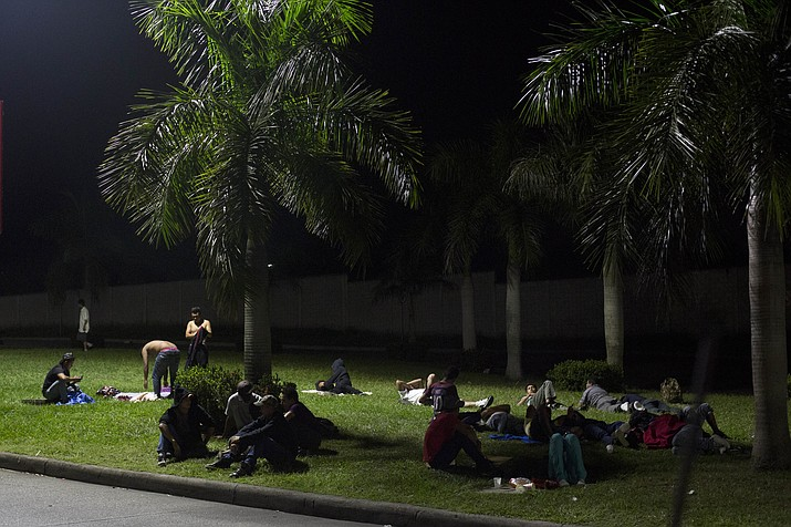 Hondurans sleep on the grass underneath palm trees, bathed by the light of street lamps outside the Metropolitan Grand Central bus terminal Oct. 31, 2018, in San Pedro Sula, Honduras. Some are awaiting buses north to the Guatemalan border to begin their journey north. Others are arriving after failing to complete the journey and will be ferried back to the lives they had planned to leave behind. (Moises Castillo/AP)