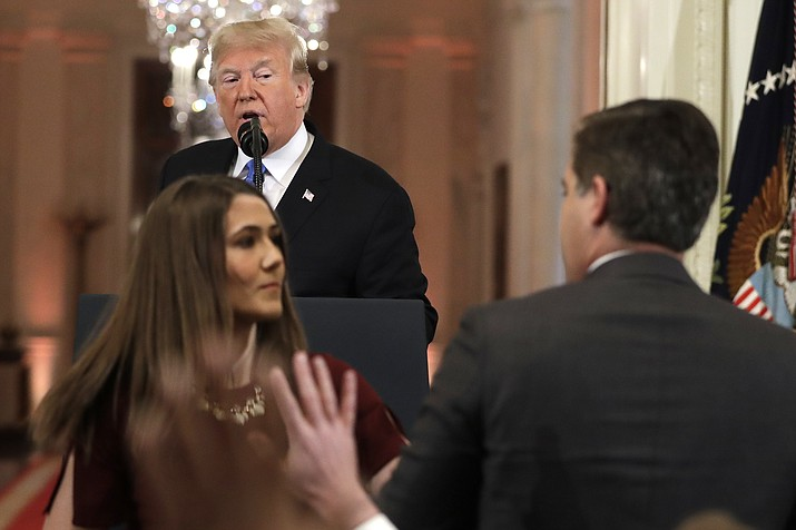 As President Donald Trump points to CNN's Jim Acosta, a White House aide takes the microphone from him during a news conference in the East Room of the White House, Wednesday, Nov. 7, 2018, in Washington. (AP Photo/Evan Vucci)
