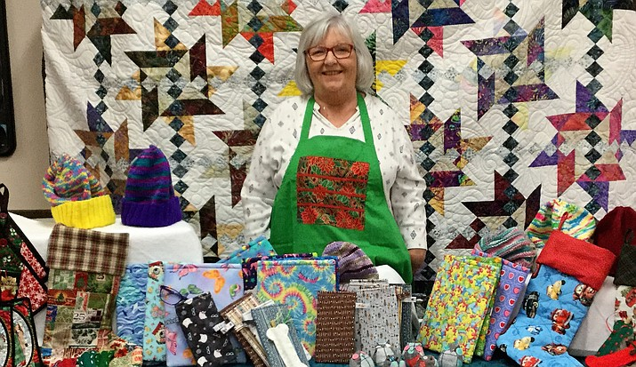 The Lonesome Valley Quilt Guild's raffle quilt (shown here behind Karen Kumke) will find a new home about 3:30 p.m. Saturday, Nov. 10, at the LVQG's Holiday Boutique from 10 a.m. to 4 p.m. at Step One Coffee House Conference Room, 6719 E. 2nd St., Prescott Valley. You need not be present to win. (Courtesy)