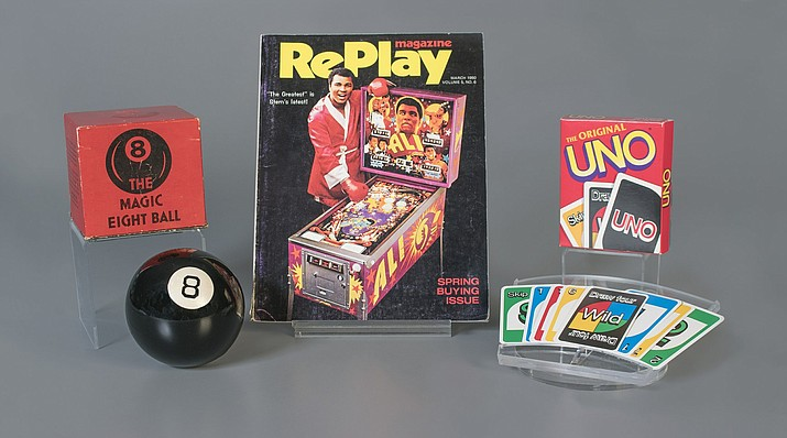 This October 2018 photo provided by The Strong museum shows the toys to be inducted into the National Toy Hall of Fame, inside the Rochester, N.Y., museum. The class of 2018 honored Thursday, Nov. 8, includes, from left, the Magic 8 Ball, pinball and the card game Uno. (Victoria Gray/The Strong via AP)