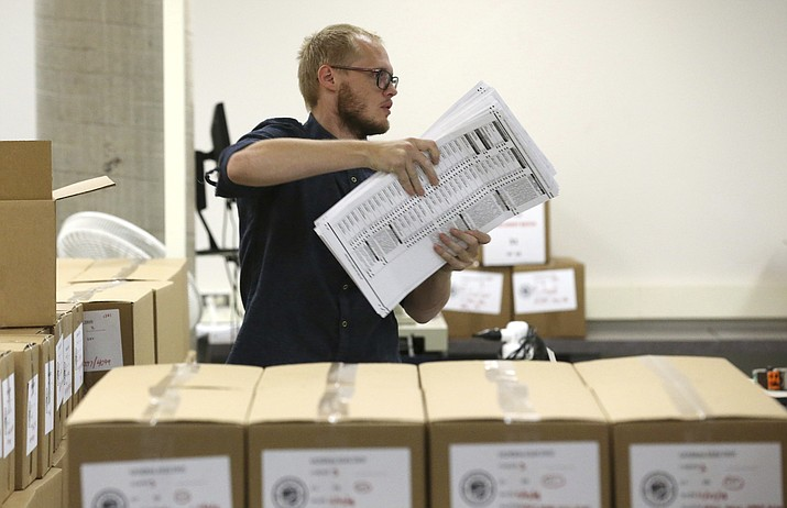 A worker carries ballots to be verified at the Maricopa County Recorder's Office Thursday, Nov. 8, 2018, in Phoenix. (Ross D. Franklin/AP)