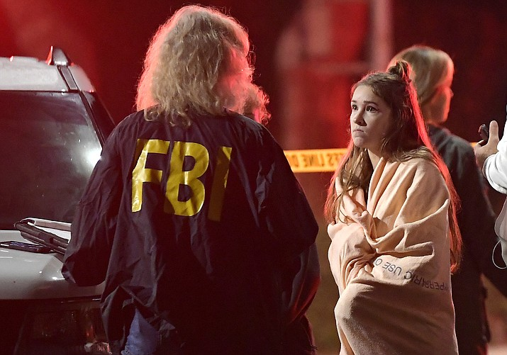 "An FBI agent talks to a potential witness as they stand near the scene Thursday, Nov. 8, 2018, in Thousand Oaks, Calif. where a gunman opened fire Wednesday inside a country dance bar crowded with hundreds of people on ""college night."" (Mark J. Terrill/AP)"
