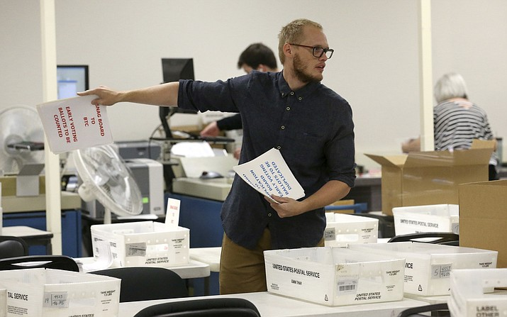 A worker prepares volunteers to verify ballots at the Maricopa County Recorder's Office Thursday, Nov. 8, 2018, in Phoenix. There are several races too close to call in Arizona, especially the Senate race between Democratic candidate Kyrsten Sinema and Republican candidate Martha McSally. (AP Photo/Ross D. Franklin)