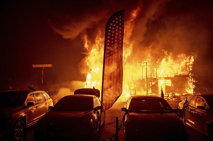 Flames consume a car dealership as the Camp Fire tears through Paradise, Calif., on Thursday, Nov. 8, 2018. (AP Photo/Noah Berger)