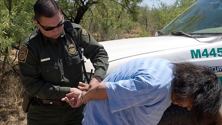 U.S. Border Patrol agent places a Mexican National under arrest for transporting drugs into the United States. (U.S. Customs and Border Protection)