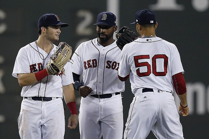 Boston Red Sox players Andrew Benintendi, Jackie Bradley Jr. and Mookie Betts celebrate beating the Twins at Fenway Park in July. A Massachusetts great-grandfather has won a $100,000 lottery prize by picking the jersey numbers of five members of the World Series-winning Red Sox. (AP file photo)