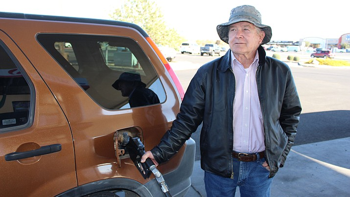 Mike Suhy wears a warm leather jacket while he gases up on a chilly Friday morning in Kingman. The National Weather Service issued the first freeze watch of the season for areas around Kingman and Pahrump, Nevada. (Photo by Hubble Ray Smith/Daily Miner)