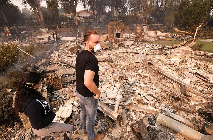 Alexander Tobolsky, right, and his girl friend Dina Arias, return to his home where burned out by the fire in Malibu, Calif., Saturday, Nov. 10, 2018. Officials took advantage of temporarily calm conditions Saturday to assess damage from the blaze that's burned 109 square miles outside downtown Los Angeles.(Ringo H.W. Chiu/AP)