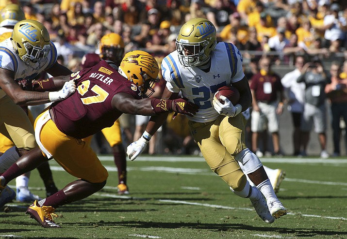 UCLA running back Joshua Kelley (27) runs the ball around Arizona State linebacker Darien Butler (37) during the first half of an NCAA college football game, Saturday, Nov. 10, 2018, in Tempe, Ariz. (Ralph Freso/AP)