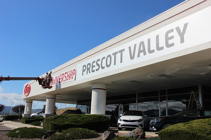 Contractors place banners on the Kia dealership in Prescott Valley Thursday, Nov. 8, to indicate it's under new ownership and has a new name: Prescott Valley Kia. (Max Efrein/Courier)