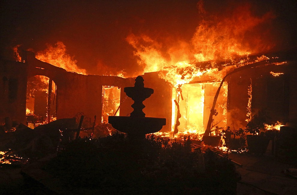 A Spanish-style home is consumed by flames on Dume Drive in the Point Dume area of Malibu, Calif., Friday, Nov. 9, 2018. Known as the Woolsey Fire, it has consumed tens of thousands of acres and destroyed multiple homes. (AP Photo/Reed Saxon)