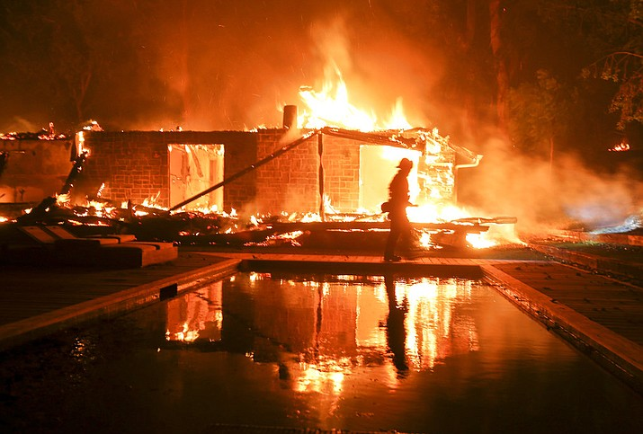 A firefighter walks by the a burning home in Malibu, Calif., Friday, Nov. 9, 2018. A Southern California wildfire continues to burn homes as it runs toward the sea. Winds are blamed for pushing the fire through scenic canyon communities and ridgetop homes. (AP Photo/Ringo H.W. Chiu)