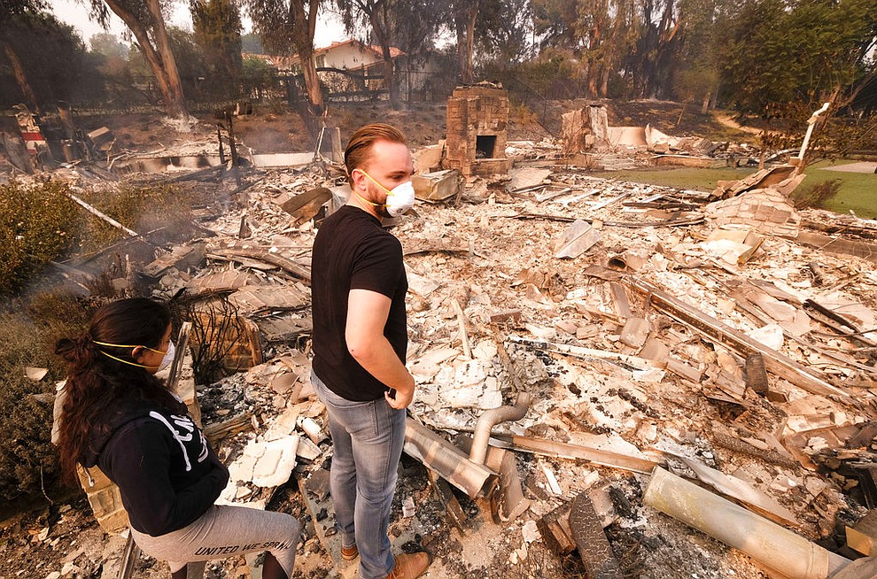 Alexander Tobolsky, right, and his girl friend Dina Arias, return to his home where burned out by the fire in Malibu, Calif., Saturday, Nov. 10, 2018.  Officials took advantage of temporarily calm conditions Saturday to assess damage from the blaze that's burned 109 square miles outside downtown Los Angeles.(AP Photo/Ringo H.W. Chiu)