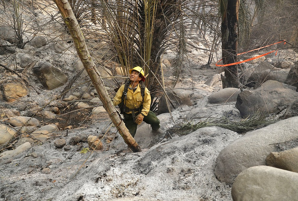 Firefighter Eric Santana, with the MRCA Fire Divison Santa Monica Mountains, looks for hot spots after a wildfire swept through Saturday, Nov. 10, 2018, in Malibu, Calif. (AP Photo/Marcio Jose Sanchez)
