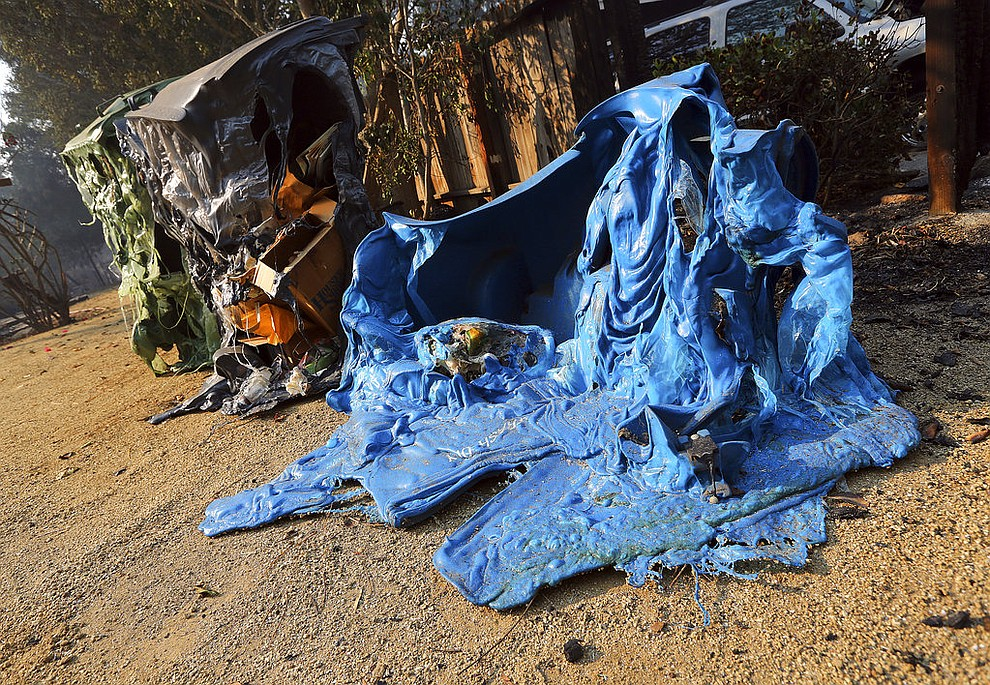 Melted recycling and trash containers stand next to one of at least 20 homes destroyed just on Windermere Drive in the Point Dume area of Malibu, Calif., Saturday, Nov. 10, 2018. Known as the Woolsey Fire, it has consumed thousands of acres and destroyed dozens of homes. (AP Photo/Reed Saxon)