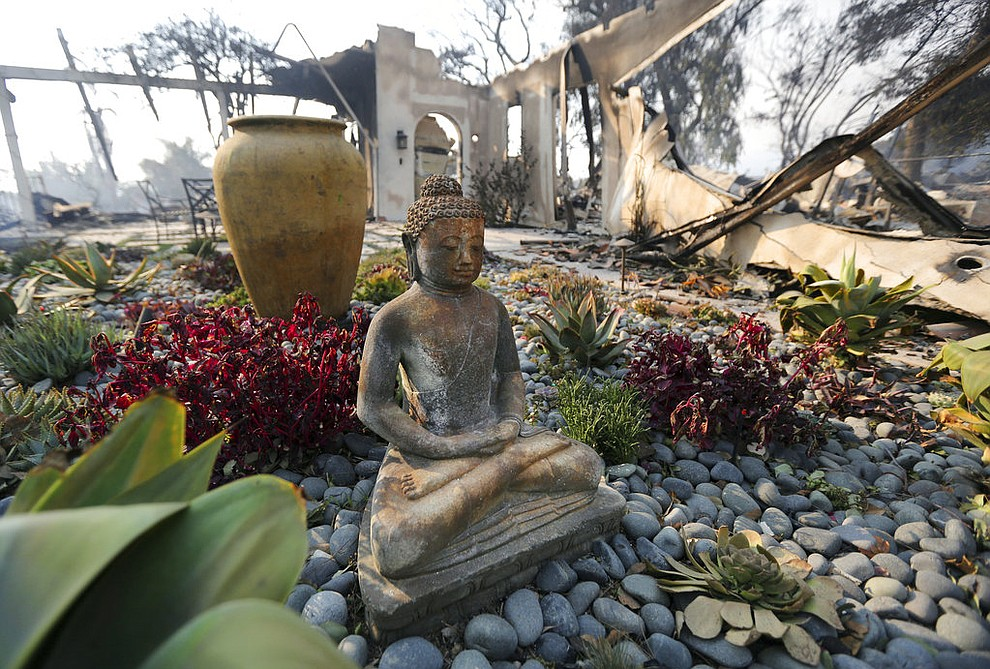 A figure of Buddha stands outside one of at least 20 homes destroyed just on Windermere Drive in the Point Dume area of Malibu, Calif., Saturday, Nov. 10, 2018. Known as the Woolsey Fire, it has consumed thousands of acres and destroyed dozens of homes. (AP Photo/Reed Saxon)