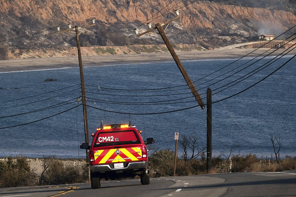 "A Los Angeles Fire Department truck drives past burned and broken telephone poles along the coast down Pacific Coast Highway which remained closed in both directions outside of Malibu, Calif., on Saturday, Nov. 10, 2018. Firefighters have saved thousands of homes despite working in ""extreme, tough fire conditions that they said they have never seen in their life,"" Los Angeles County Fire Chief Daryl Osby said. (AP Photo/Richard Vogel)"