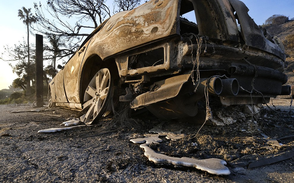 "The charred out remains of a car that burned after a wildfire swept through along the Pacific Coast Highway in Malibu, Calif., on Saturday, Nov. 10, 2018. Firefighters have saved thousands of homes despite working in ""extreme, tough fire conditions that they said they have never seen in their life,"" Los Angeles County Fire Chief Daryl Osby said. (AP Photo/Richard Vogel)"
