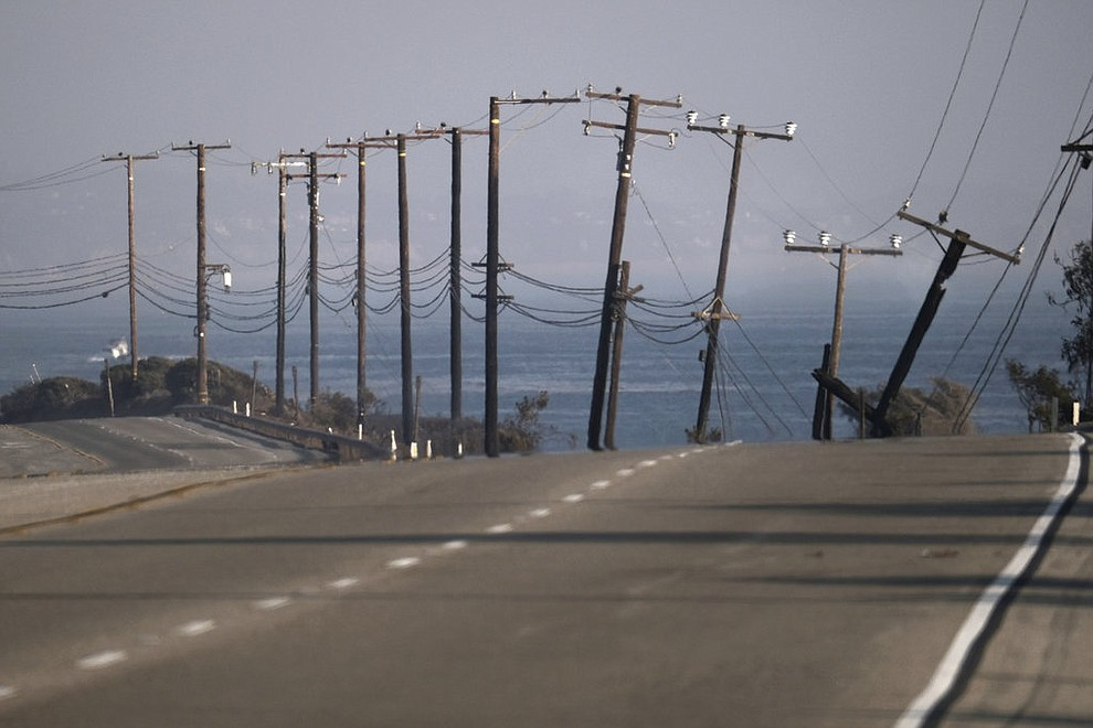 "The remains of broken telephone poles line the Pacific Coast Highway which remained closed in both directions after a wildfire swept through to the area outside of Malibu, Calif. on Saturday Nov. 10, 2018. Firefighters have saved thousands of homes despite working in ""extreme, tough fire conditions that they said they have never seen in their life,"" Los Angeles County Fire Chief Daryl Osby said. (AP Photo/Richard Vogel)"