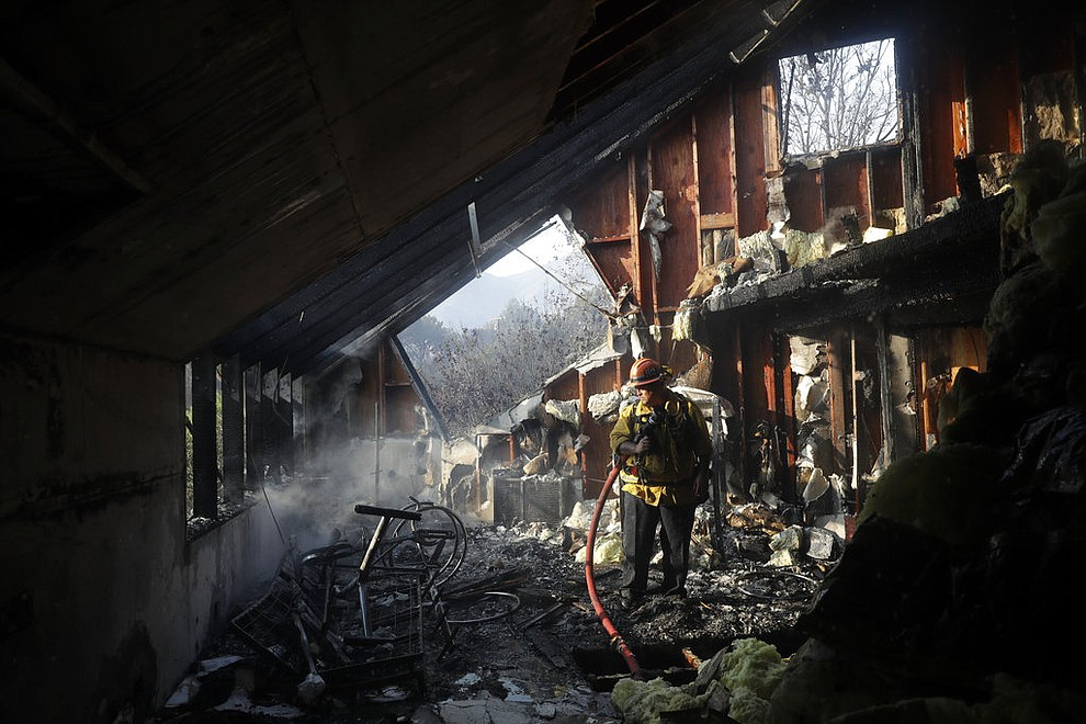 Capt. Adrian Murrieta with the Los Angeles County Fire Dept., looks for hot spots on a wildfire-ravaged home Saturday, Nov. 10, 2018, in Malibu, Calif. Scores of houses from ranch homes to celebrities' mansions burned in a pair of wildfires that stretched across more than 100 square miles of Southern California, authorities said Saturday. (AP Photo/Marcio Jose Sanchez)