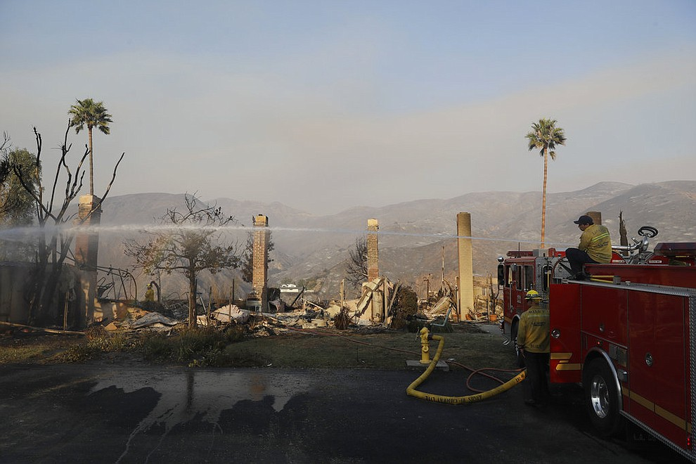 Firefighters hose down hot spots on a wildfire-ravaged property Saturday, Nov. 10, 2018, in Malibu, Calif. Scores of houses from ranch homes to celebrities' mansions burned in a pair of wildfires that stretched across more than 100 square miles of Southern California, authorities said Saturday. (AP Photo/Marcio Jose Sanchez)
