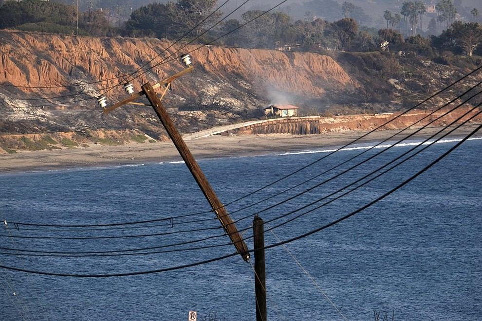 A smoldering hillside is seen in the distance behind a broken and burned telephone pole hanging along the Pacific Coast Highway outside of Malibu, Calif. on Saturday Nov. 10, 2018. (AP Photo/Richard Vogel)